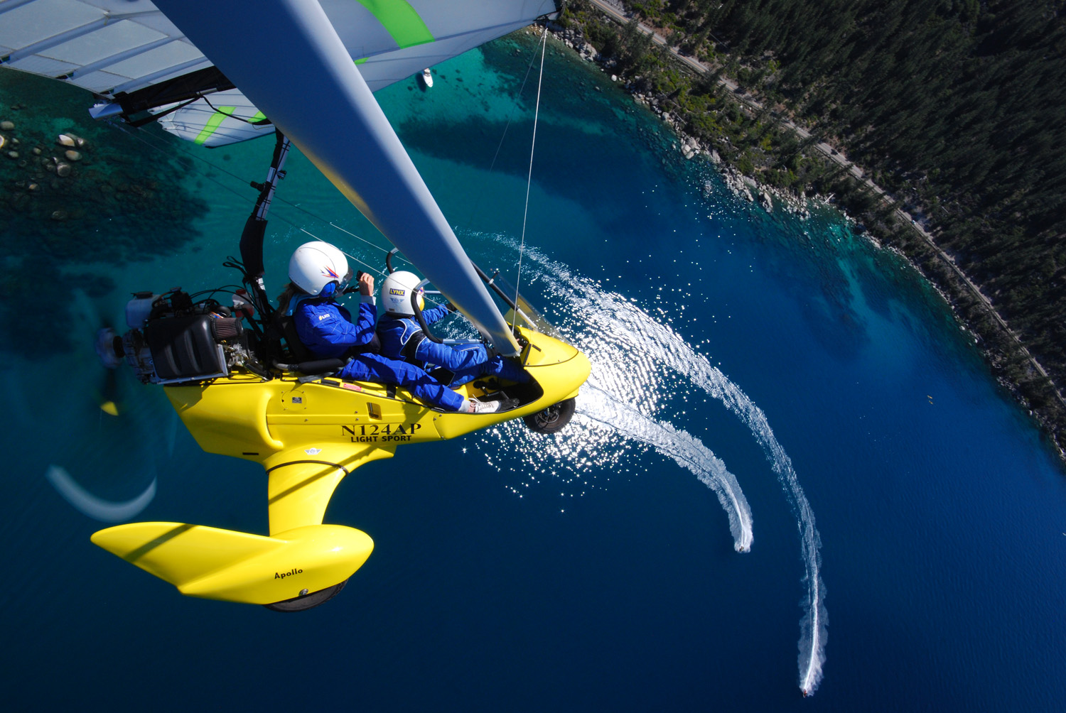 Powered hang glider above two boats on Lake Tahoe - Hang Gliding Tahoe