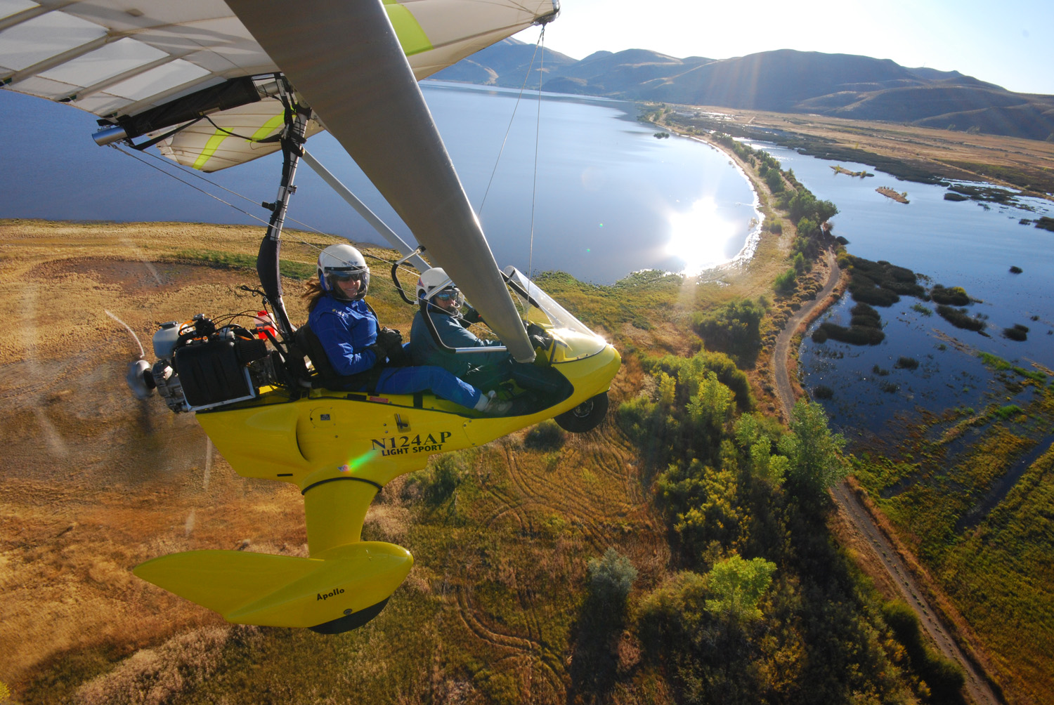 Student pilot smiles while flying powered hang glider by Washoe Lake, Nevada - Hang Gliding Tahoe
