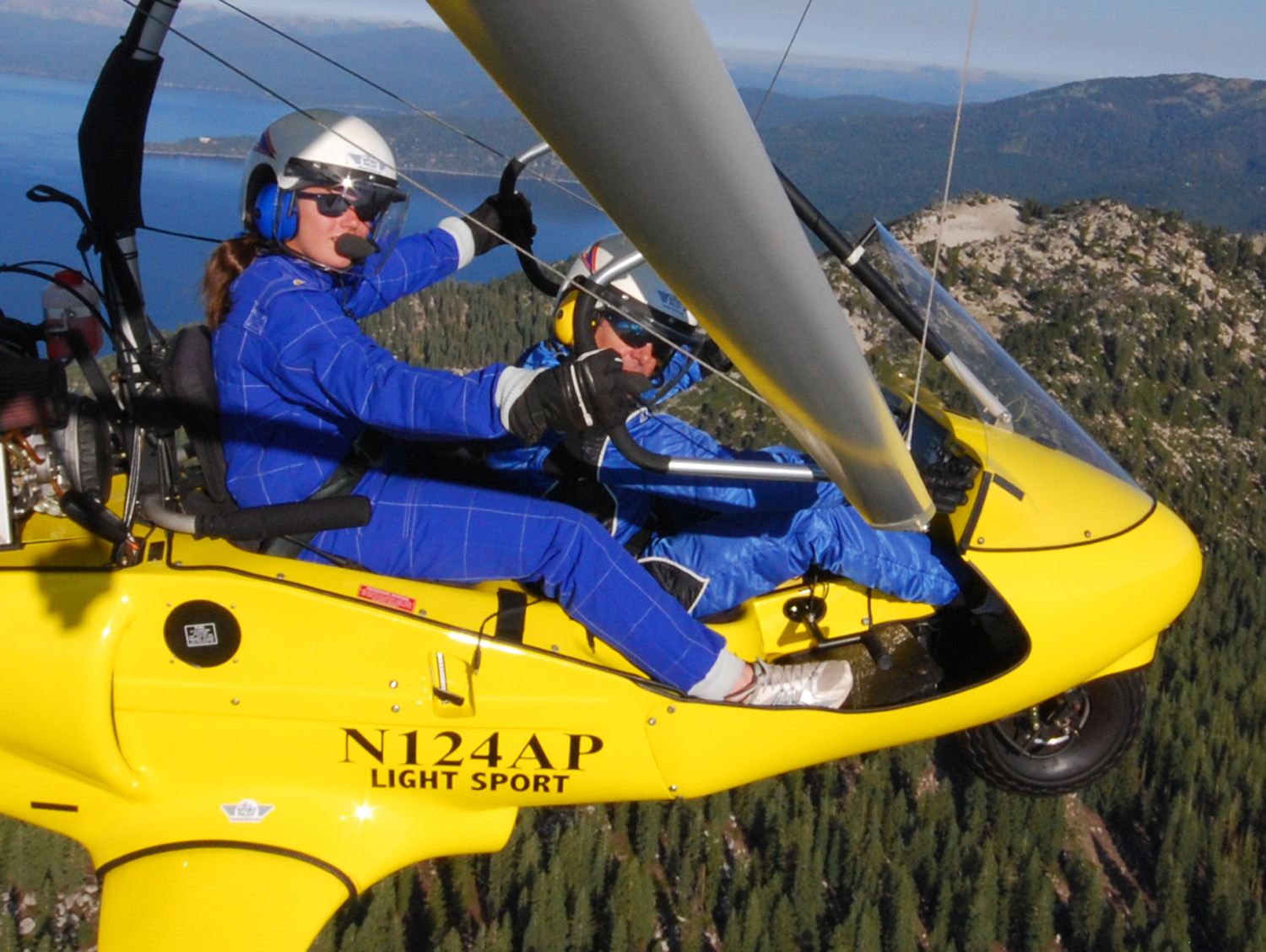 Student at controls flying powered hang glider above Lake-Tahoe, Hang Gliding Tahoe