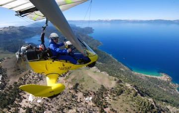 Student flying powered hang glider, Marlette Lake and Lake Tahoe in background, Hang Gliding Tahoe