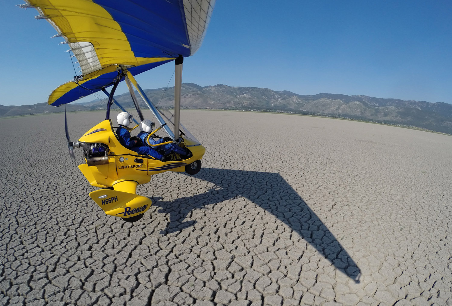 Skimming low over dry lake bed in powered hang glider.
